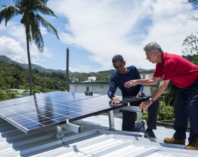 In this July 24, 2018 photo, Julio Rosario, left, instals a solar energy system with the founder of the nonprofit environmental group Casa Pueblo Alexis Masol, in Adjuntas, Puerto Rico. The nonprofit environmental group Casa Pueblo has installed solar systems at two hardware stores, one barber shop and several corner stores that activists hope will serve as a power oasis where people can charge their phones and store medications during a storm if needed. (AP Photo/ Dennis M. Rivera Pichardo)