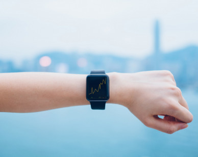 Financial trading data shown on smart watch on human hand against urban city skyline